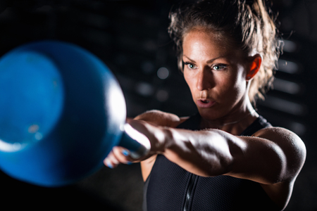 Photo pour Woman athlete exercising with kettlebell indoors - image libre de droit