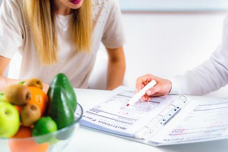 Foto de Doctor nutritionist, dietician and female patient on consultation in the office - Imagen libre de derechos
