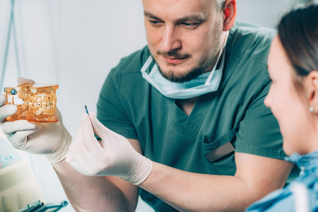 Photo for Dentist explaining dental implant procedure to patient in clinic - Royalty Free Image