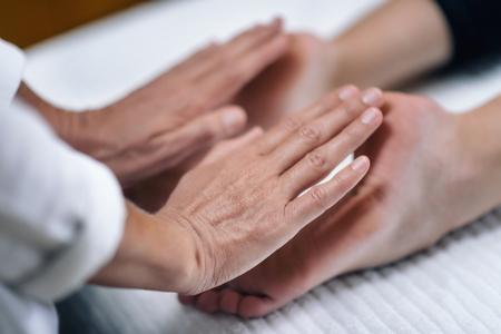 Foto de Hands of Reiki therapist healing and balancing feet chakras. Energy healing concept - Imagen libre de derechos