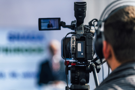 Photo pour Cameraman wearing headphones and recording male speaker standing on the stage at press conference media event. - image libre de droit