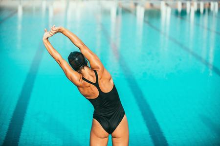 Female warming up for swimming. Stamding on pool edge and warming up hands and shoulders