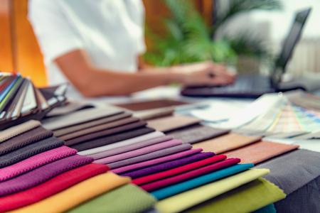 Photo pour Female interior designer choosing furniture materials samples in a studio - image libre de droit