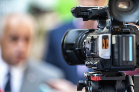 Camera operator working at a press conference outdoors. Journalists interviewing formal dressed politician or businessman at a media event.