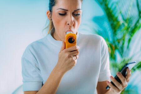 Photo pour Woman Using Portable Spirometer and a Smart Phone App - image libre de droit