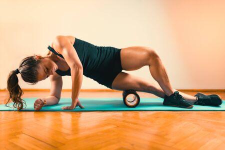 Foto für Sporty Woman Massaging Her Legs with Foam Roller - Lizenzfreies Bild