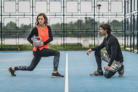 Foto de Personal fitness trainer working with young woman, doing kettlebell exercises, outdoors. - Imagen libre de derechos