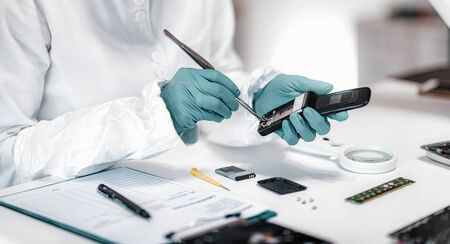 Foto de Digital Forensic Science. Police Forensic Analyst Examining Confiscated Mobile Phone. - Imagen libre de derechos