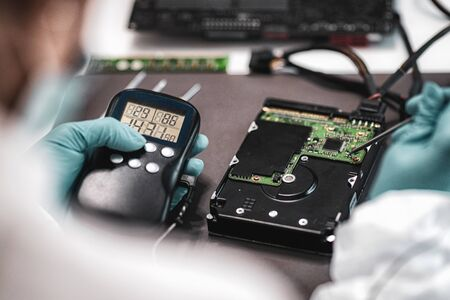 Photo for Digital Forensic Science. Police Forensic Analyst Examining Computer Hard Drive. - Royalty Free Image
