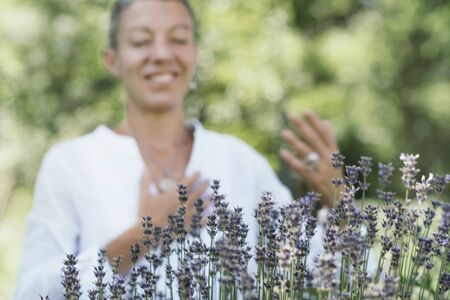 Photo for Gratitude - Natural beauty middle age model smiling and expressing gratitude to the nature with hands. Healing Through Nature - Giving and receiving energy concept. - Royalty Free Image
