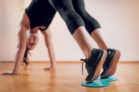Foto de Female Athlete Exercising with Sliding Discs. - Imagen libre de derechos