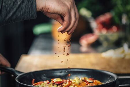 Photo for Sprinkling ground red chili pepper paprika over sliced vegetables, motion blur  - Royalty Free Image