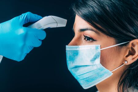 Photo pour Coronavirus. Medical worker in hazmat protective suite checking body temperature, woman with protective mask - image libre de droit
