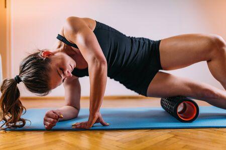 Photo pour Sporty Woman Self Massaging Legs with Foam Roller at Home - image libre de droit
