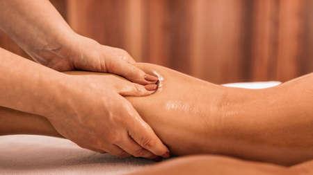 Photo pour Lymphatic drainage massage. Hands of a masseuse massaging leg of a female client - image libre de droit