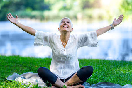Photo pour Mindful senior woman, feeling overwhelmed by beauty of the, meditating, sitting by the water with open arms - image libre de droit