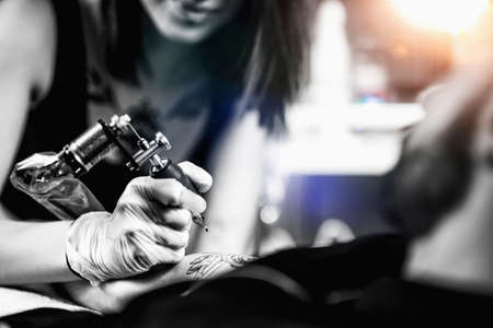 Photo for Professional female tattooist working in a tattoo studio - Royalty Free Image