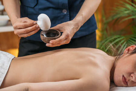 Photo pour Kizhi or Herbal Bags Ayurveda Massage. Ayurvedic massage practitioner dipping cotton-wrapped herbal bundle into aromatic oil. - image libre de droit