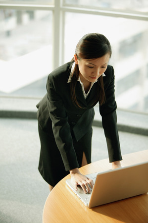 Young woman standing, using laptop