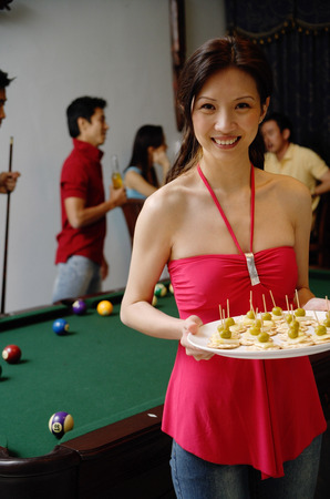 Party host with plate of appetizers, smiling at camera