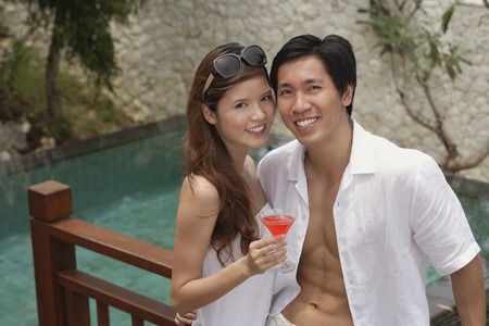 Couple standing side by side, smiling at camera, swimming pool behind themの写真素材