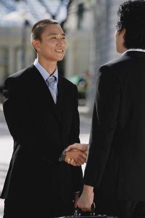 Two men wearing suits greet each other and shake hands in the park