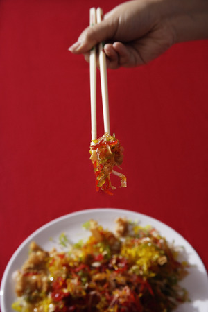 Woman tossing raw fish salad also known as 'Yu Sheng' or 'Lo Hei'