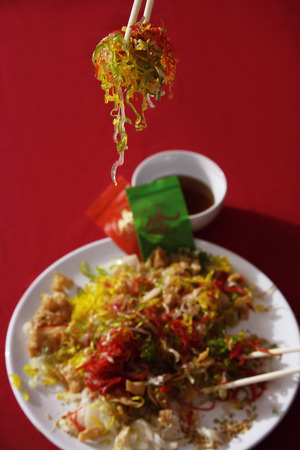 Tossing raw fish salad also known as 'Yu Sheng' or 'Lo Hei'
