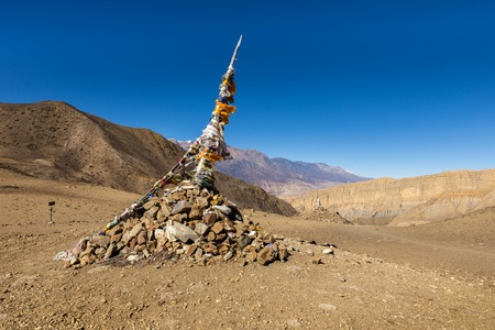 traditional tibetan pile of stones and colored flags