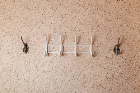 Photo pour White metal hangers for clothes on the background wall - image libre de droit