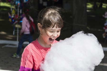 Young girl eating cotton candy in the park.