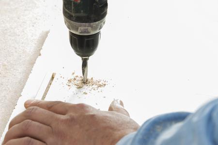 worker drills a hole when assembling furniture