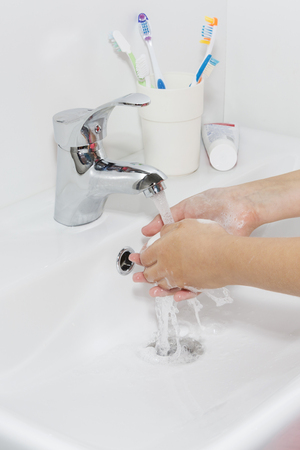 Hygiene concept. Washing hands with soap under the faucet with water.