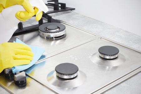 Photo pour Cleaning a gas stove with kitchen utensils, household concepts, or hygiene and cleaning. - image libre de droit