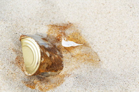 Photo pour an old rusty tin can left by a man on a sandy beach - image libre de droit