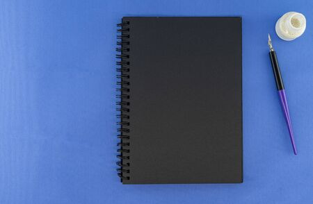 black Notepad with pen and ink on a blue background