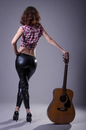 Young woman with an acoustic guitar on a black background, rear view. A woman in leather pants and a shirt posing while standing, holding a guitar.