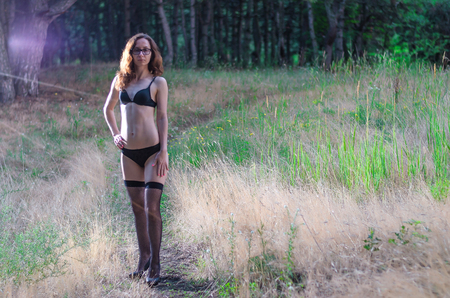 A young woman in lingerie and stockings is standing in the forest, a copy of the free space.