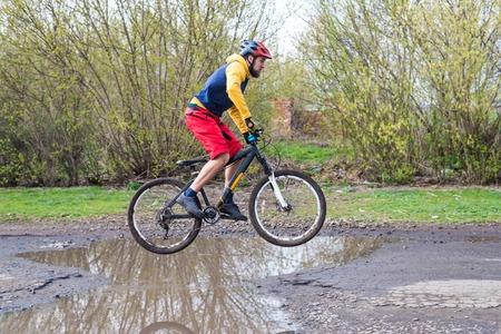 Photo for A cyclist in red shorts and a yellow jacket riding a bicycle on the rear wheel through a puddle. Active way of life in the fresh air. - Royalty Free Image
