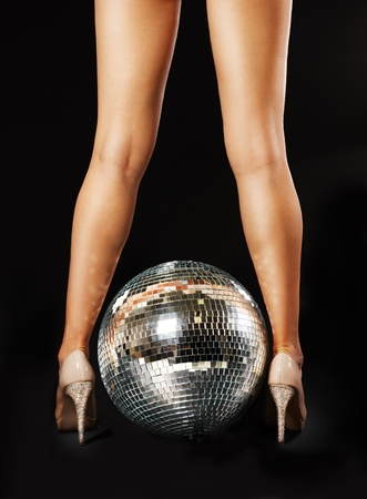 Tanned female legs with disco ball over black backgroundの写真素材