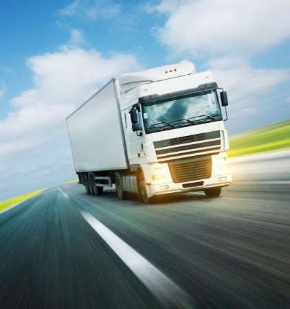 Photo pour White truck on asphalt road under blue sky with clouds - image libre de droit