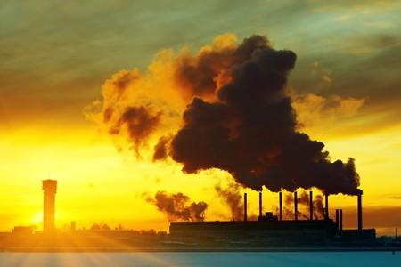 Power plant with smoke under sunset light