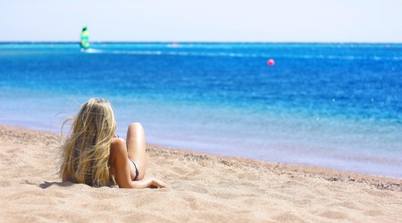 Young blonde woman lying on sand near sea