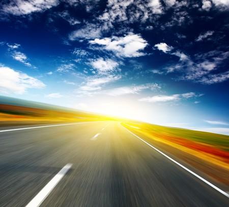 Photo pour Blurred asphalt road and blue sky with clouds and light spot - image libre de droit