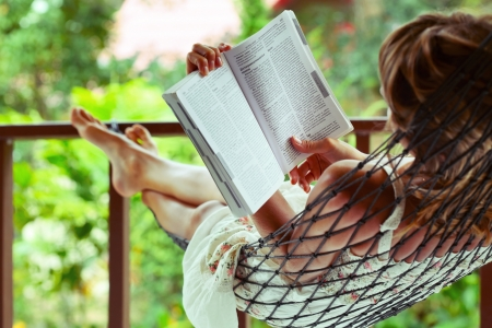 Photo pour Young woman reading a book lying in a hammock - image libre de droit
