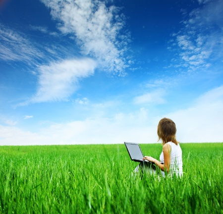 Young woman with laptop sitting on green grass and looking to a blue cloudy sky