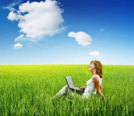 Young woman sitting with laptop on green grass and looking to a sky.