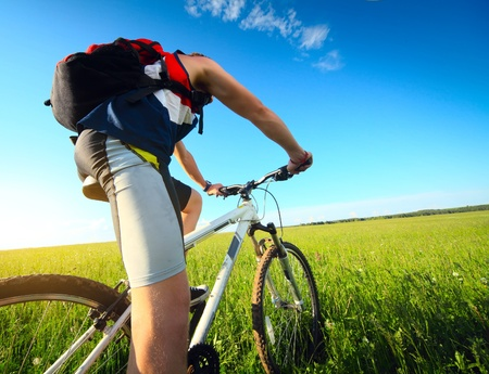 Foto de Young man riding on a bicycle on green meadow with a red backpack - Imagen libre de derechos