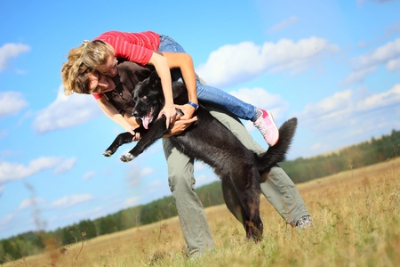 Young family having fun with their big dog on a countryside meadow.