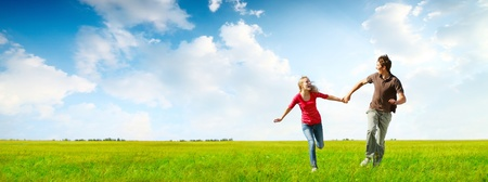 Photo for Young happy couple running on a green meadow with blue cloudy sky on the background - Royalty Free Image